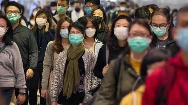 Пассажиры в медицинских масках в переходе метро, Китай