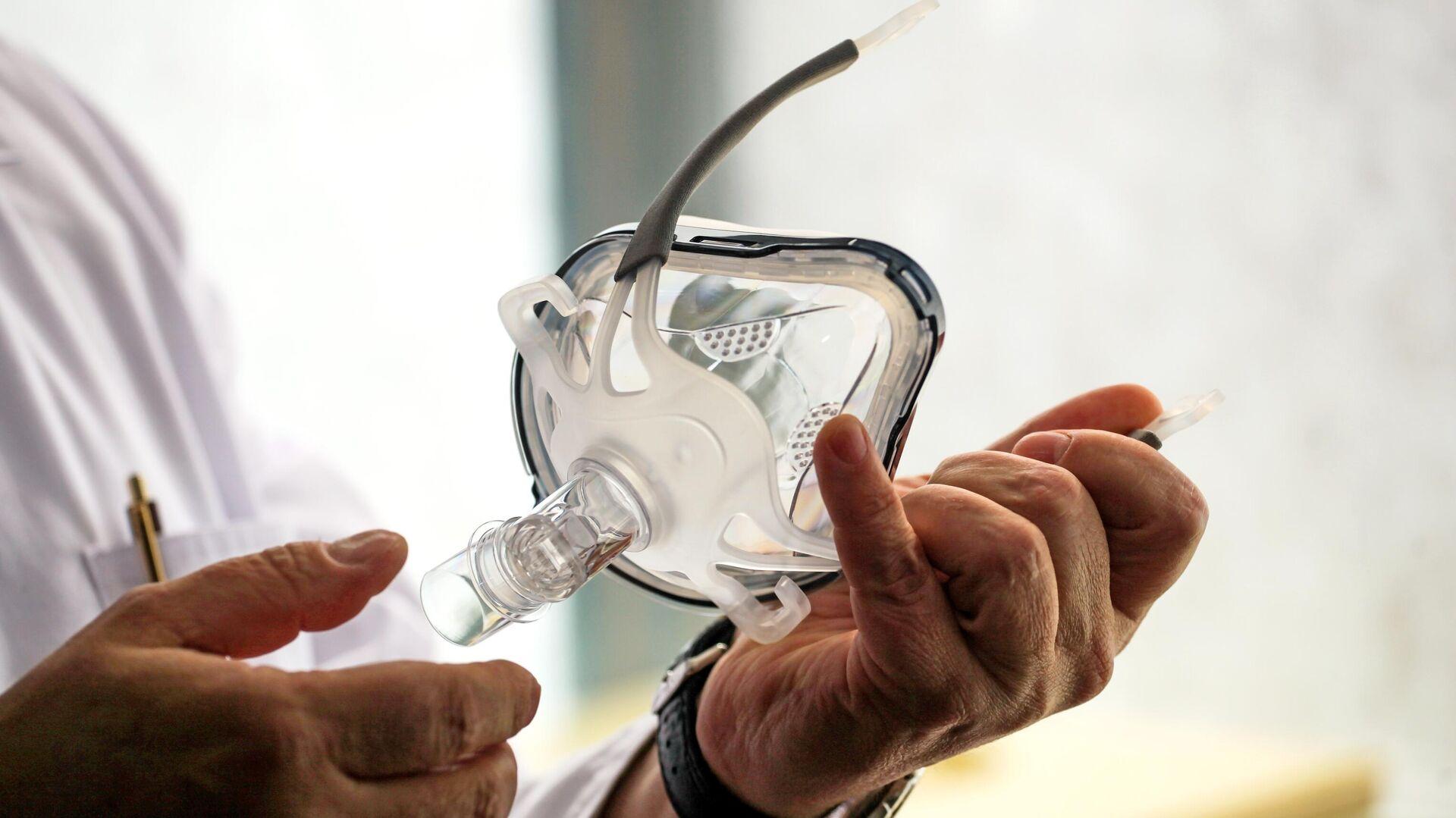 Врач держит в руках маску для искусственной вентиляции легких - РИА Новости, 1920, 17.10.2020