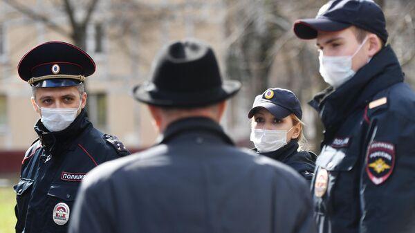 Сотрудники полиции разговаривают с пожилым мужчиной на улице