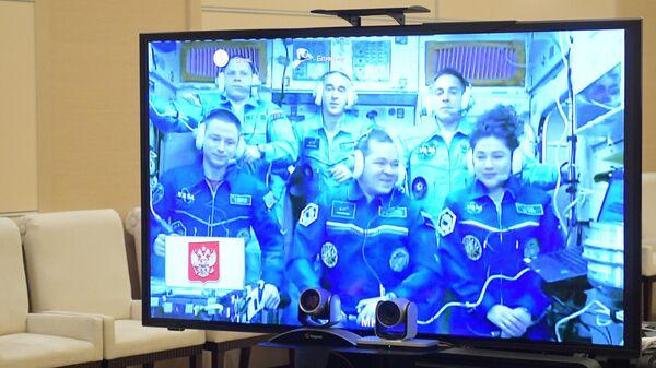 Экипаж Международной космической станции на экране во время сеанса связи с президентом РФ Владимиром Путиным