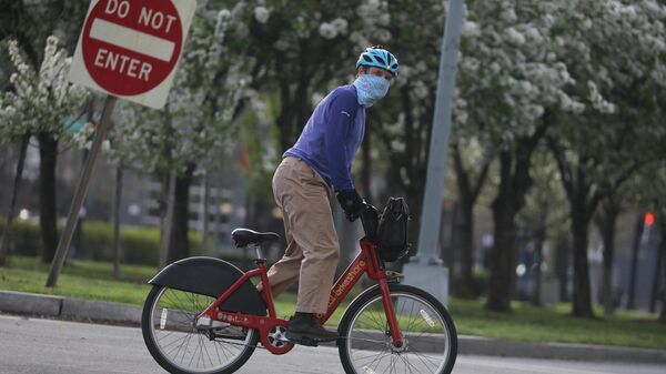 Велосипедист в маске во время вспышки коронавируса в Вашингтоне