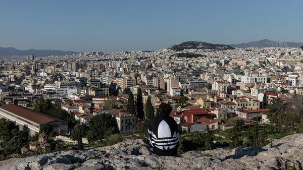 Молодой человек на холме Акрополь в Афинах