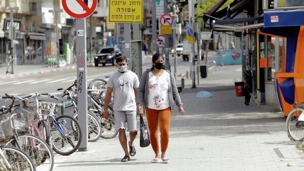 Прохожие в медицинских масках на одной из улиц Тель-Авива
