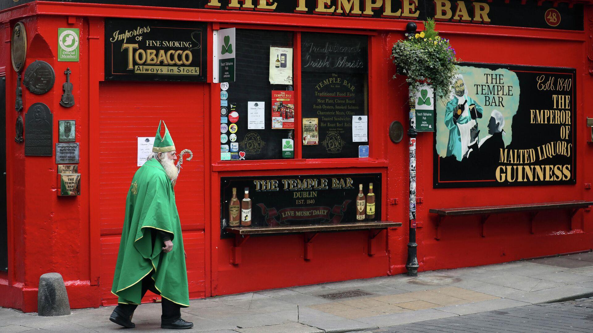 Мужчина в костюме Святого Патрика проходит мимо паба в Дублине  - РИА Новости, 1920, 16.09.2021
