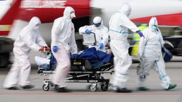 Медицинские работники везут пациента с коронавирусной инфекцией в Дрездене, Германия