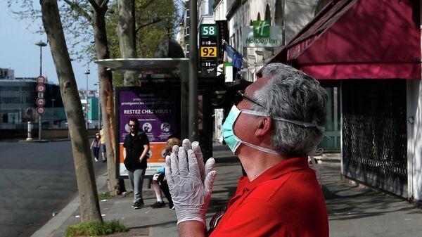 Мужчина в защитной маске на улице Парижа, Франция