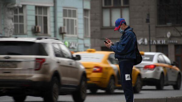 Мужчина в защитной маске вызывает такси наа Тверской улице во время режима самоизоляции жителей в Москве