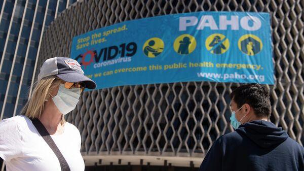 Люди в масках у здания Всемирной организации здравоохранения в Вашингтоне