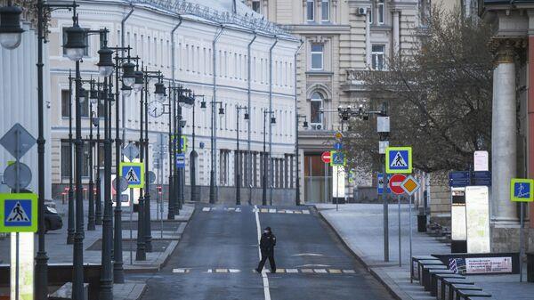 Сотрудница полиции переходит дорогу во время режима самоизоляции жителей в Москве