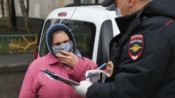 Сотрудник полиции проводит оповещение граждан на одной из улиц в Москве