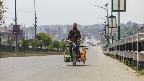 Мужчина в защитной маске едет на велосипеде по пустой улице в Катманду