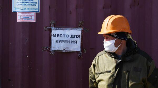 Рабочий в медицинской маске на строительстве жилого комплекса Приозерный компании Энергомонтаж в Новосибирске