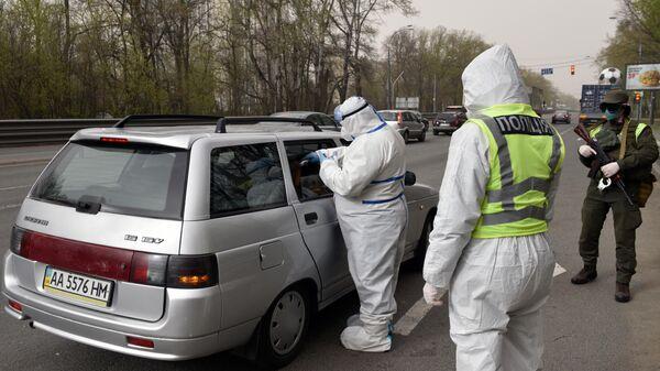 Сотрудники полиции на блокпосту измеряют температуру пассажиров и водителей автомобилей на въезде в Киев
