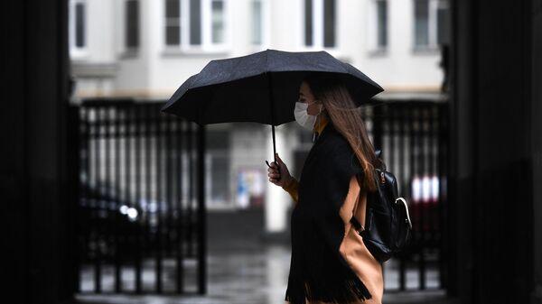 Девушка под зонтом на одной из улиц Москвы