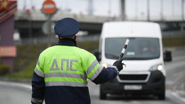 Инспектор дорожно-патрульной службы останавливает водителя для проверки