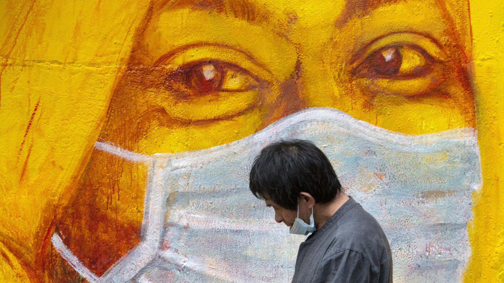 Прохожий около стены с изображением человека в маске в Гонконге - РИА Новости, 1920, 18.10.2020