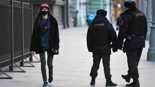 Девушка и сотрудники полиции на улице Охотный ряд в Москве