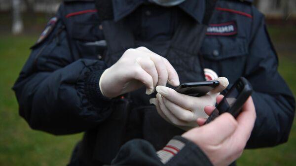 Сотрудник полиции проверяет цифровой пропуск у прохожего в Москве