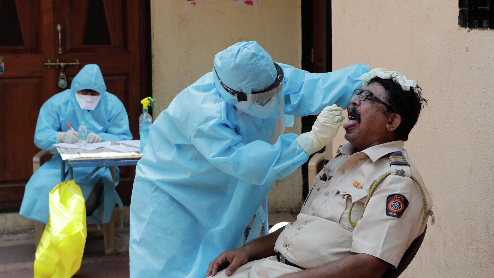 Врач берет мазок на коронавирус в бесплатном медицинском центре в трущобах Дхарави в Мумбаи, Индия - РИА Новости, 1920, 13.09.2020