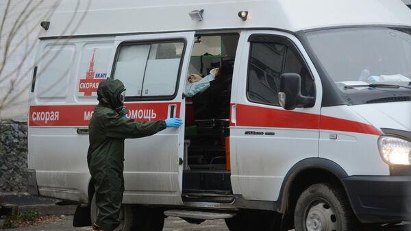 Медицинский работник в защитном костюме у здания Центральной городской клинической больницы No 1 в Екатеринбурге