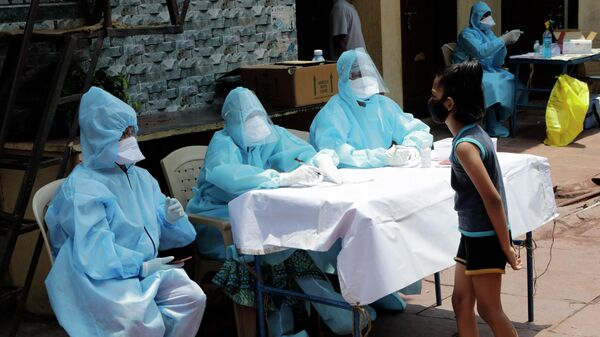 Врачи врачи беседуют с девочкой в бесплатном медицинском лагере в трущобах Дхарави в Мумбаи, Индия
