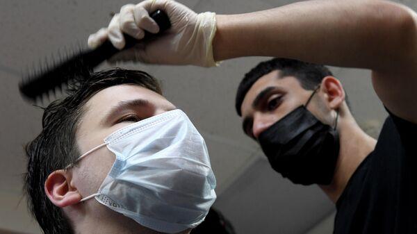 Посетитель в защитной маске в парикмахерской Супермен
