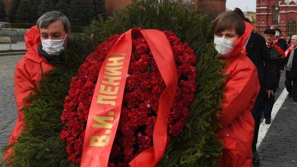 Сторонники партии КПРФ несут венок к Мавзолею В. И. Ленина по случаю 150 лет со дня его рождения