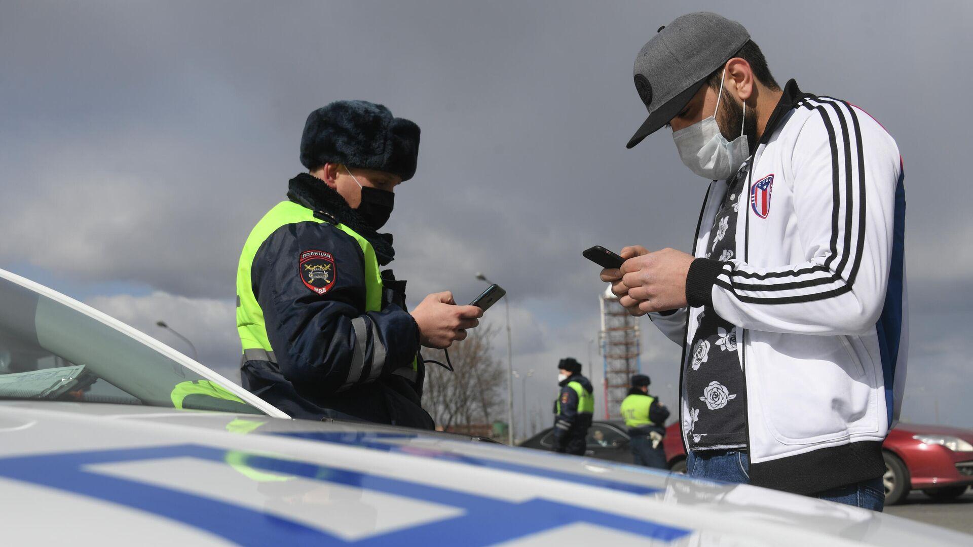 Инспектор дорожно-патрульной службы проверяет у водителя цифровой пропуск на передвижение по Москве - РИА Новости, 1920, 22.04.2020
