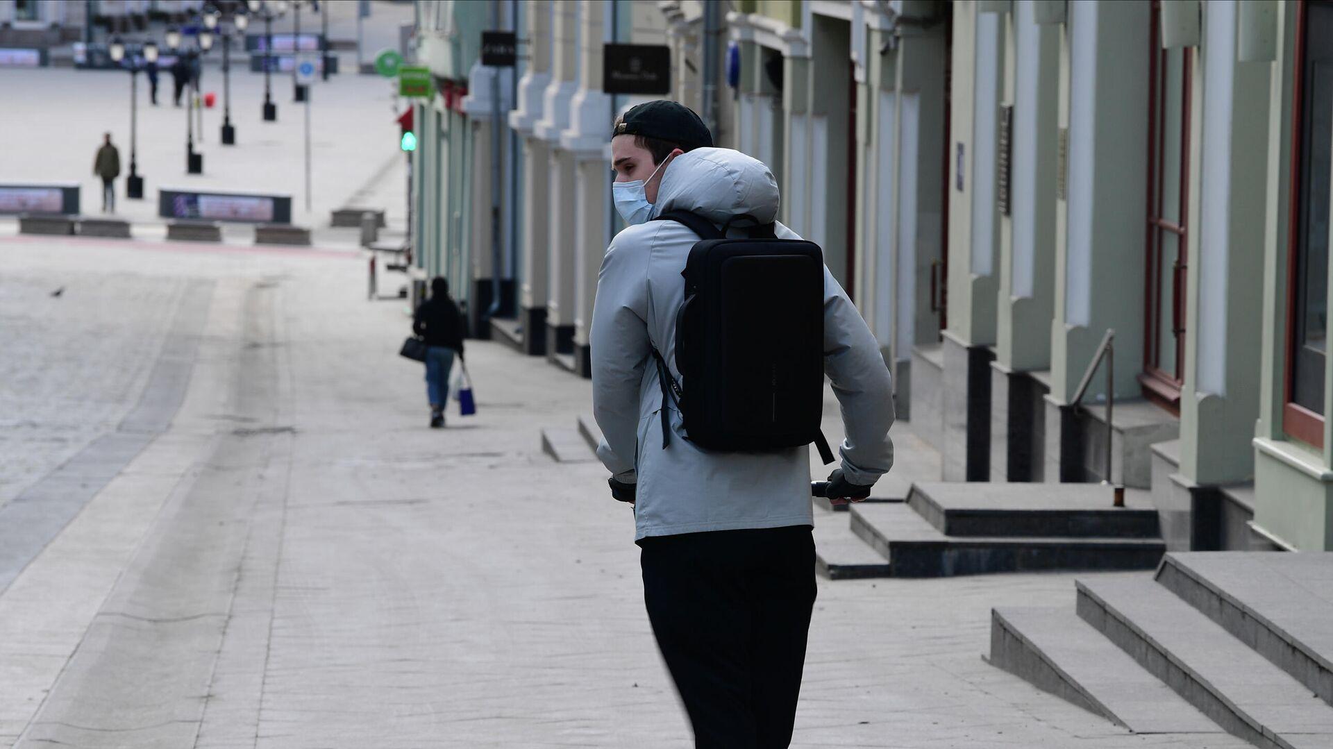 Молодой человек в защитной маске на самокате на улице Кузнецкий мост в Москве  - РИА Новости, 1920, 23.04.2020