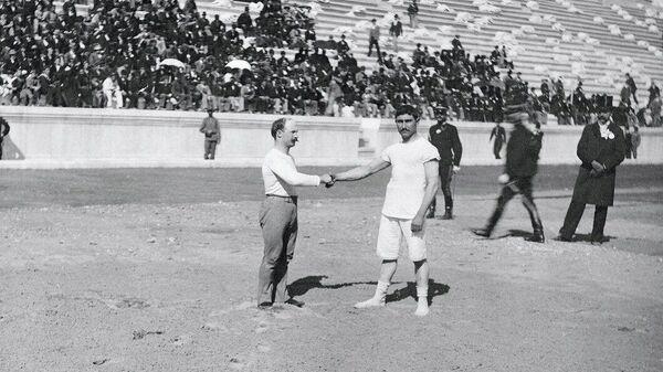 Победитель Олимпийских Игр 1896 года по гимнастике Карл Шульман (слева) принимает поздравления