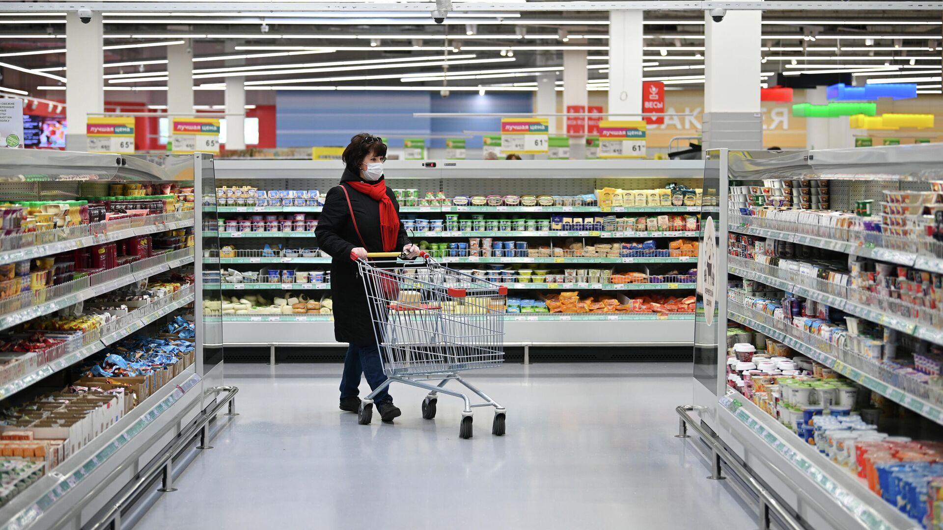 Женщина в защитной маске покупает продукты в гипермаркете - РИА Новости, 1920, 11.12.2020