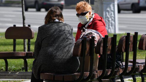 Женщины в защитных масках отдыхают в сквере на проспекте Независимости в Минске