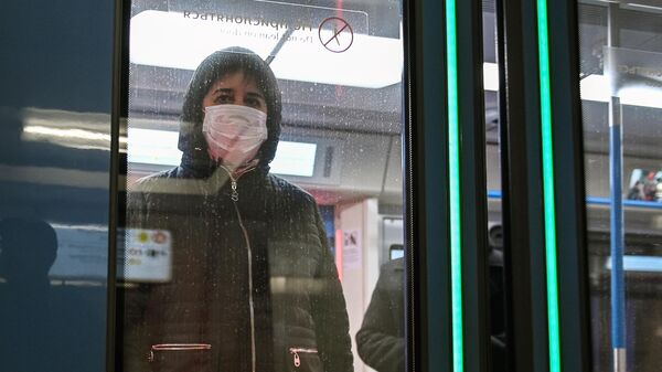 Женщина в защитной маске в вагоне поезда на станции метро Новокузнецкая в Москве