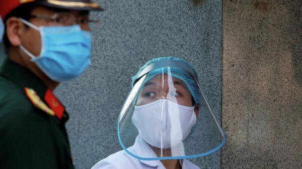 Медицинский работник в защитной маске рядом с солдатом, возле больницы во время вспышки коронавирусна в Ханое, Вьетнам