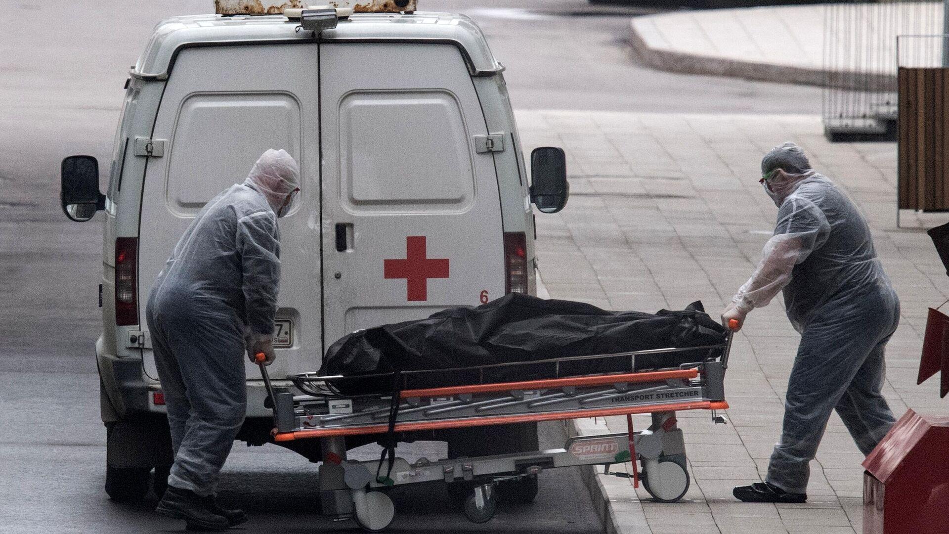 Медицинские работники перевозят тело умершего на территории карантинного центра в Коммунарке - РИА Новости, 1920, 28.09.2021