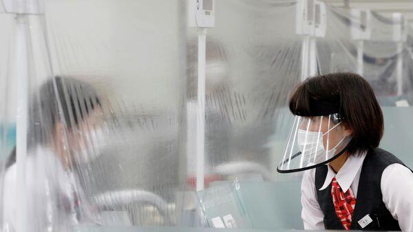 Сотрудники банка MUFG в Токио общаются при использовании средств персональной защиты
