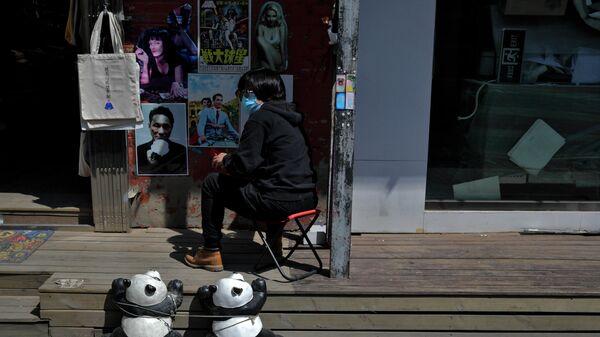 Женщина в защитной медицинской маске на улице у сувенирного магазина в Пекине, Китай