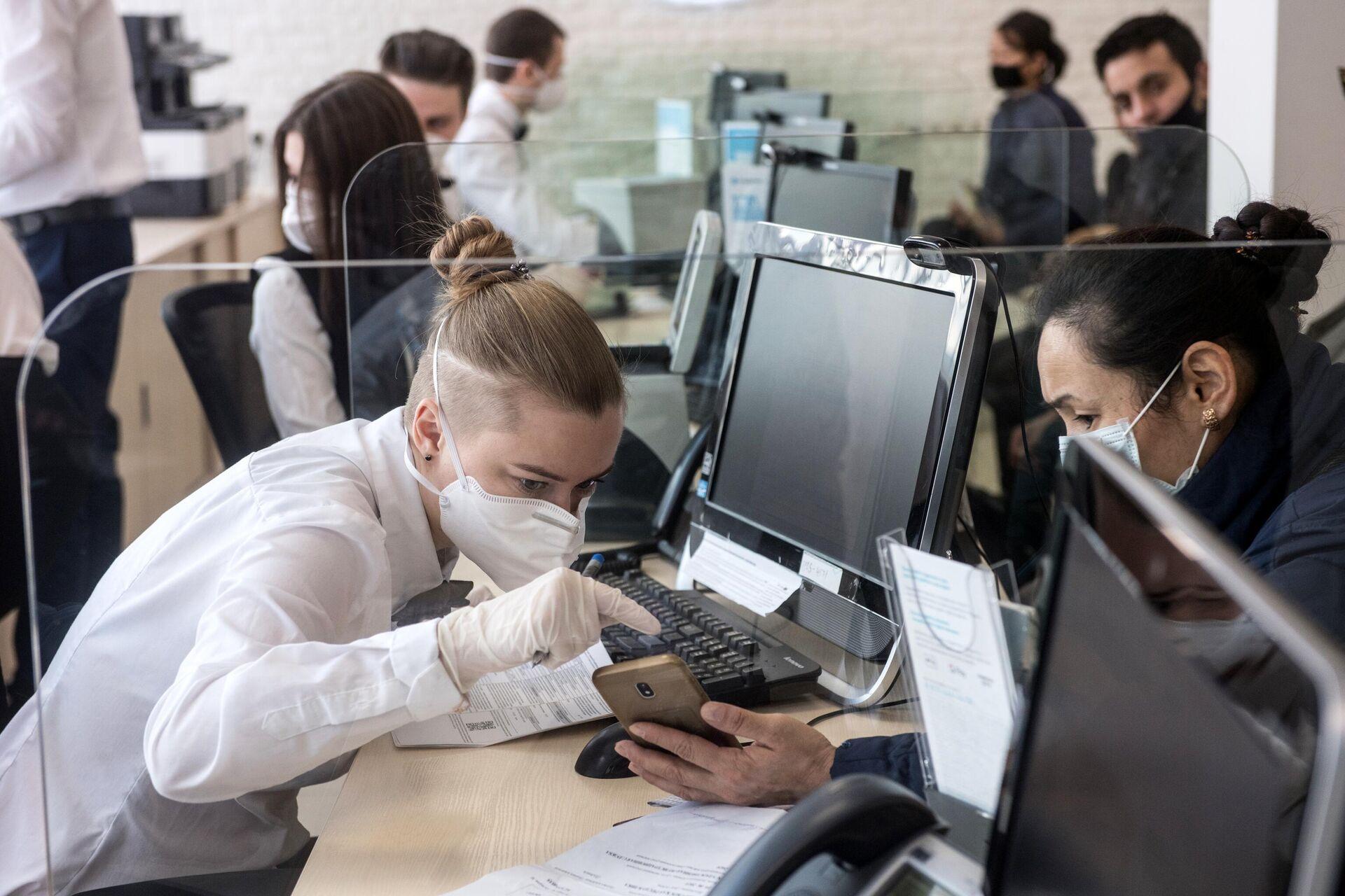 Сотрудница в защитной маске ведет прием посетителей в одном из отделений банка Открытие - РИА Новости, 1920, 08.09.2021
