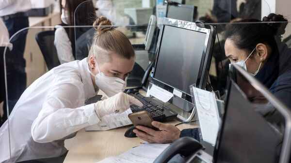 Сотрудница в защитной маске ведет прием посетителей в одном из отделений банка Открытие