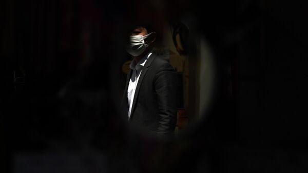 Мужчина в защитной маске в Токио, Япония