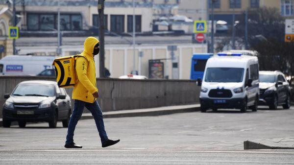 Курьер службы доставки Яндекс. Еда в защитной маске на одной из улиц Москвы