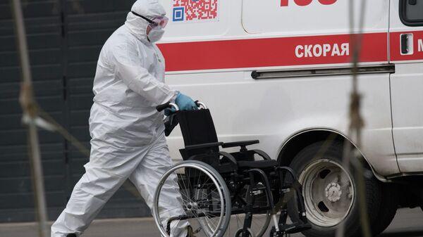 Медик везет инвалидное кресло к машине скорой медицинской помощи