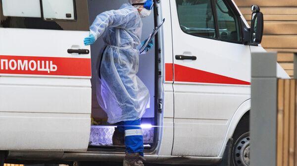 Медик выходит из машины скорой медицинской помощи