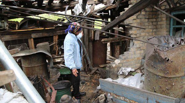 Жительница поселка Шахты 6-7 в Горловке показывает разрушения на территории своего хозяйства после обстрела