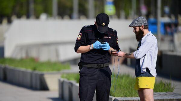 Сотрудник полиции проверяет документы у мужчины на роликах на Москворецкой набережной в Москве