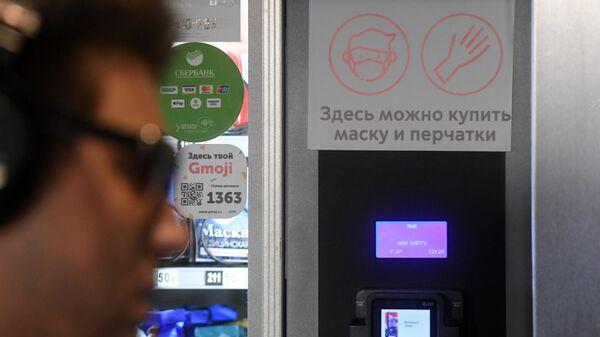 Покупатель у автомата по продаже наборов индивидуальных средств защиты в вестибюле станции Московского метрополитен