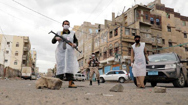 Сотрудники службы безопасности в защитных масках в Сане, Йемен