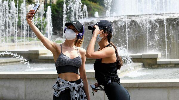 Девушки в защитных масках фотографируются на площади Кастелло в Милане