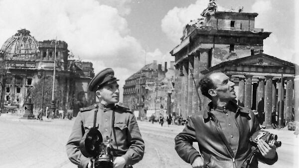 Фронтовые кинооператоры-напарники Илья Аронс (слева) и Леон Мазрухо у Бранденбургских ворот и Рейхстага. Берлин, май 1945 год