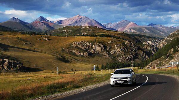 Машина едет по федеральной автомобильной дороге Чуйский тракт в Республике Алтай